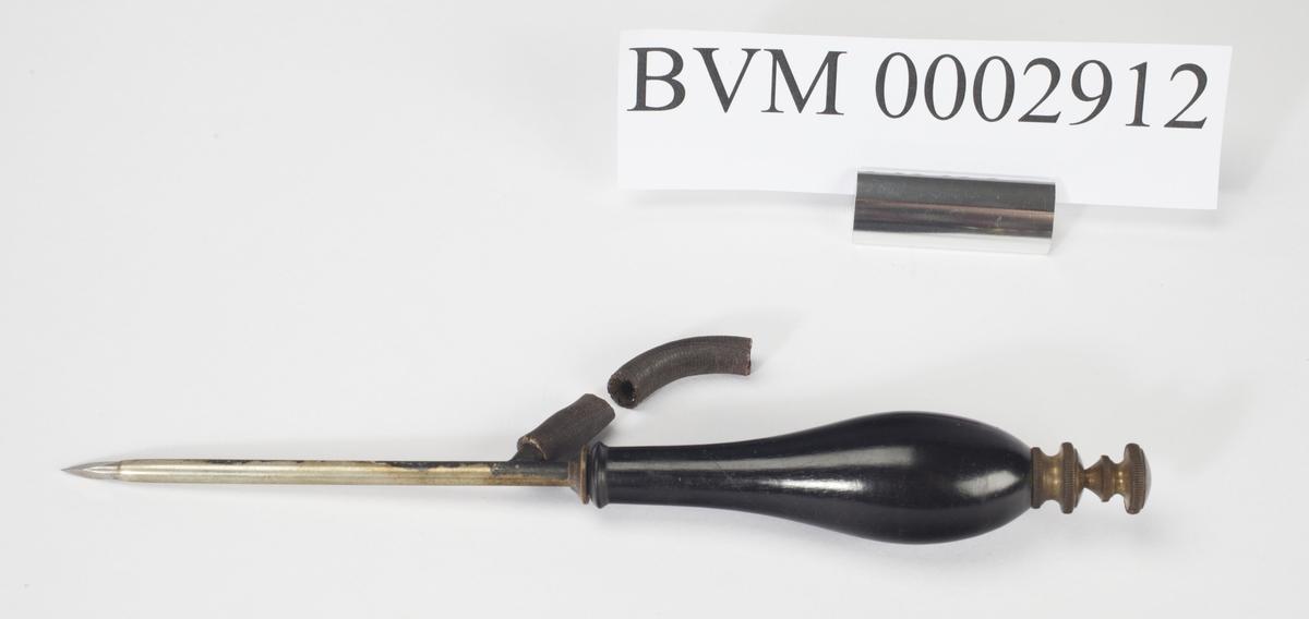 Syllignende instrument med av stål med svart lakkert treskaft. Øverst mot håndtaket et siderør av gummi. En liten del av gummirøret er knekt av.