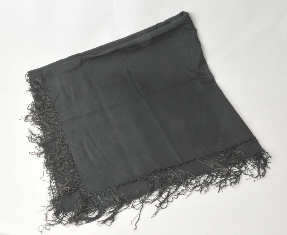 Tynt, svart, maskinvove ulltøy, kypertbinding. Påknytte silkefrynser.