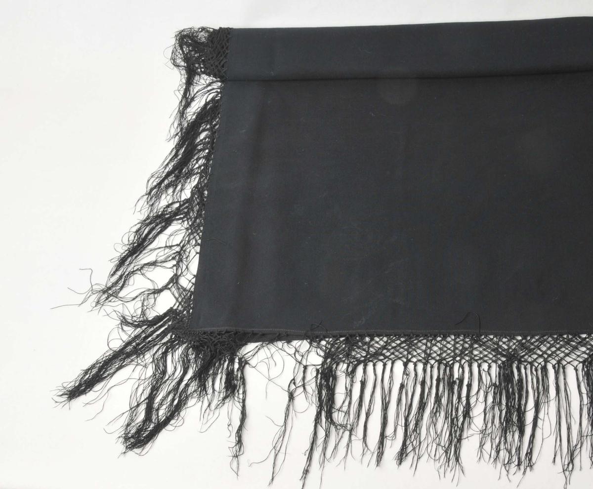 Tynt,svart, maskinvove ulltøy, kyptert-binding. Frynser med knutar rundt alle sider. Jarekant i to sider og falda dobbelt (0,5 cm faldbredde) til vranga på dei to andre.