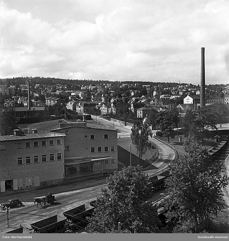 Stadsvy fotograferad från hamnen, Järnvägsparken, mot Södermalm. Närmast syns korsningen Köpmangatan/Landsvägsallén och Parkgatan samt järnvägen som går under Köpmangatan vid gasverket. I nedre vänstra hörnet syns en man som kör en häst ner mot hamnen.