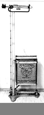 Stathmos Fix personvåg från Nya Aktiebolgaet Stthmos, Nynäshamn, Sweden.Gjutjärnsbottenplatta, fotplatta av trä, bastustav som bär upp skalan samt förnicklad skala 0 - 120 kg. Neg.nr. 1760/79, 1761/79