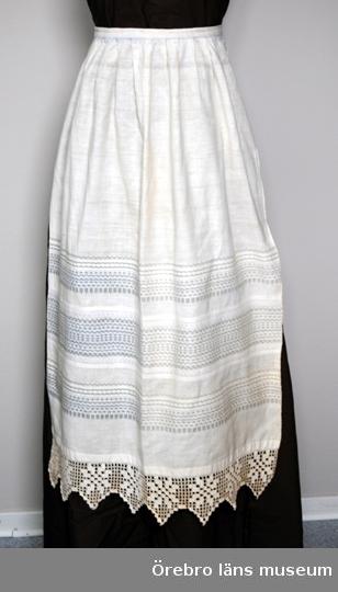 Förkläde - dam - av vitt bomullstyg, hemvävt.Midjeförkläde, har övre delen enfärgad, småveckad, med smal rand av ljusblå rosengång närmast den smala linningen. Denna fortsätter i knytband av 1,6 cm brett band, randat i vitt, blått och rött. Nedre delen av förklädet har breda grupper av rosengångsrandning i grått, ljusblått och vitt. Nerkanten har en bred, virkad uddspets av bomullsgarn.Inlämnat i samband med Städarveckan i Örebro, 18-24 april.