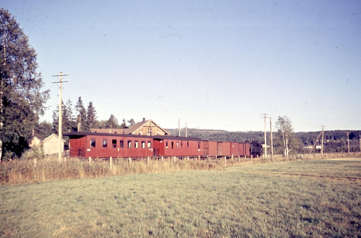 Ettermiddagstoget til Bjørkelangen, tog 2075, ved Liermosen. Bak toget ses Holen gård