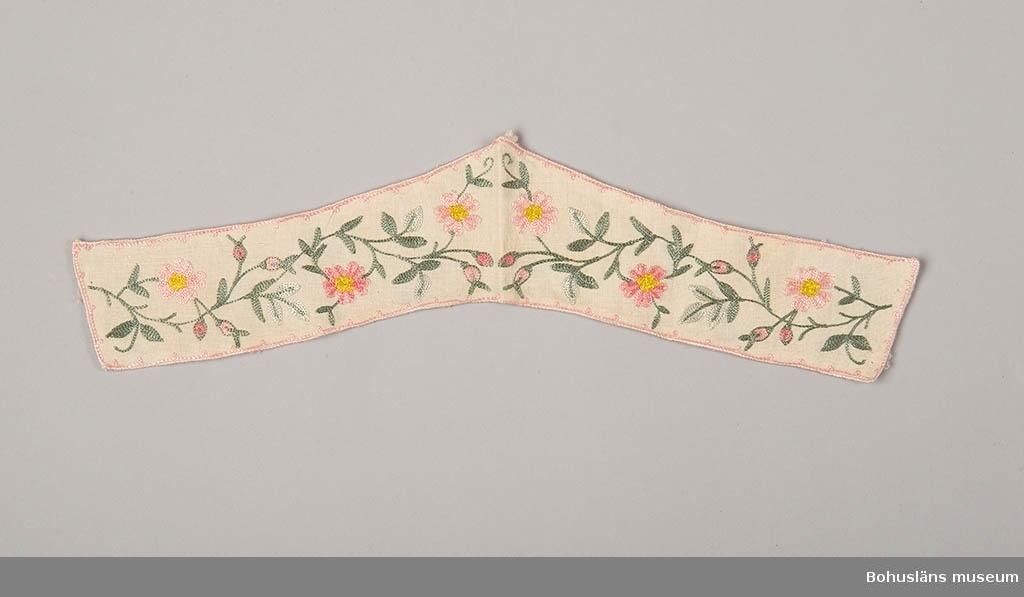 Gråa kvist och bladslingor, röda och gula blommor och knoppar i kedjesöm.  V-formad krage.
