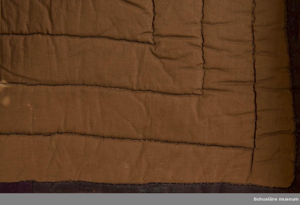 Fyra olika mönstrade sidentyger (delar av schaletter) kombinerat med enfärgat svart sidentyg; kviltat.  Brunt fodertyg i bomull. Slitet, insektsangrepp och fuktfläckar.