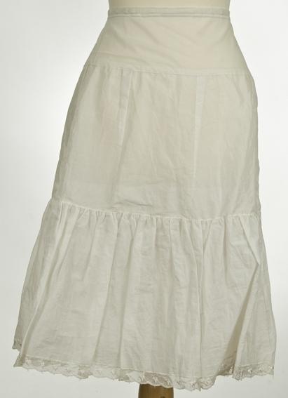 Glatt hoftestykke med strikk i livet, 2 kapper, blonde på nederste kappe.