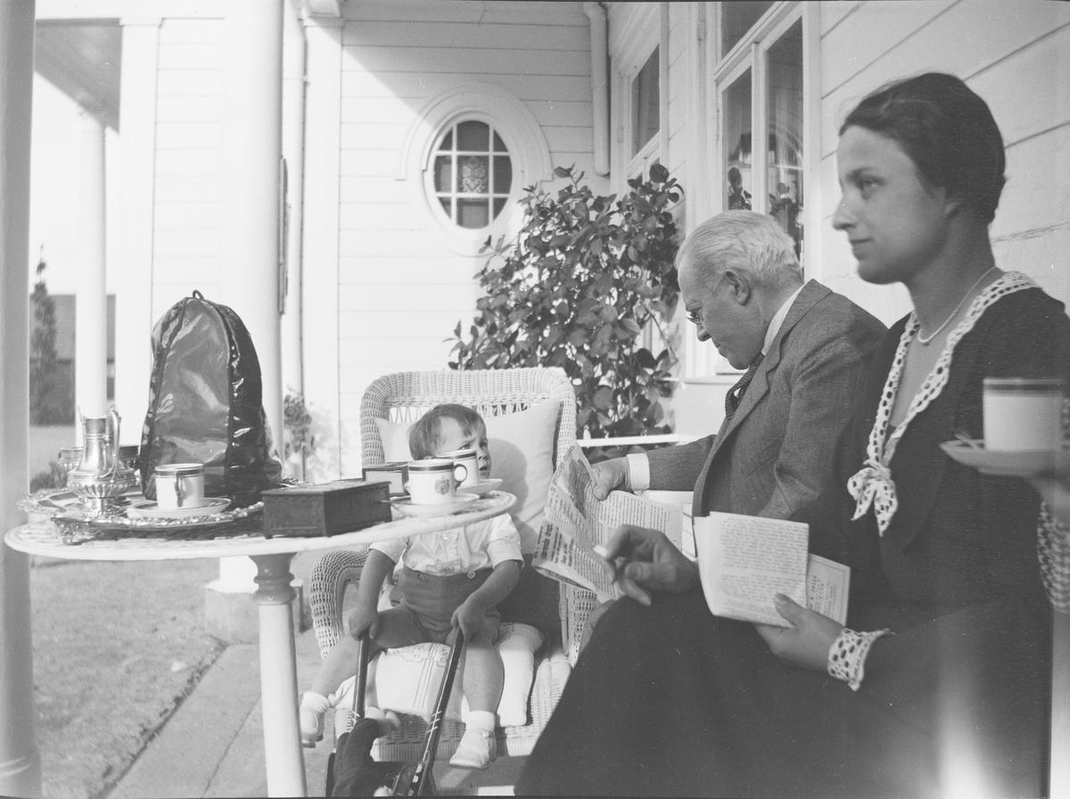 En mann, Christian Pierre Mathiesen, sitter sammen med en dame og en liten gutt på en uteplass ved inngangspartiet til hovedhuset. De snakker sammen, leser post, aviser m. m. Tre generasjoner ved et kaffe- og/eller tebord. Det er sommer på Linderud Gård.
