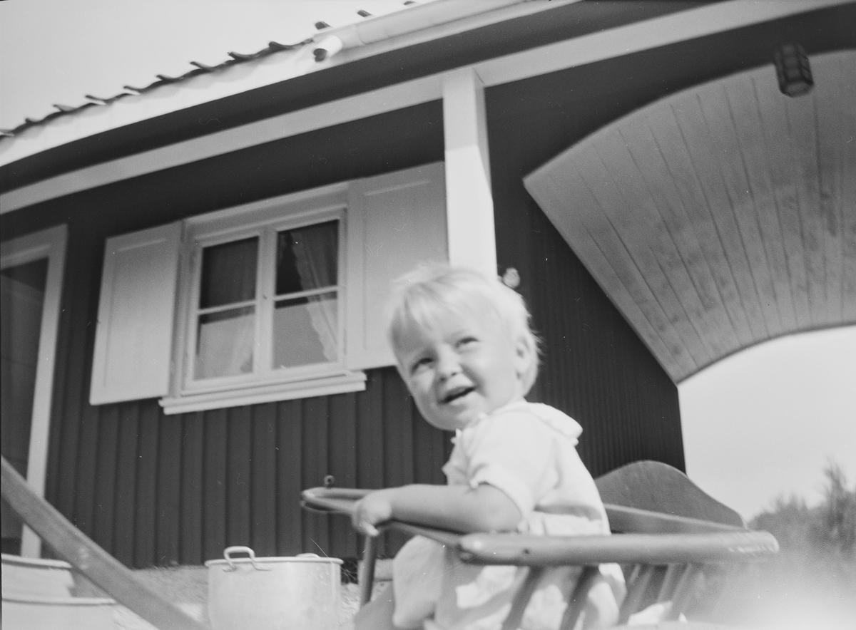 """En liten gutt, """"Lillefar"""", sitter i en barnestol foran et hus som består av to deler. De to delene har felles tak, en portal utgjør skillet."""