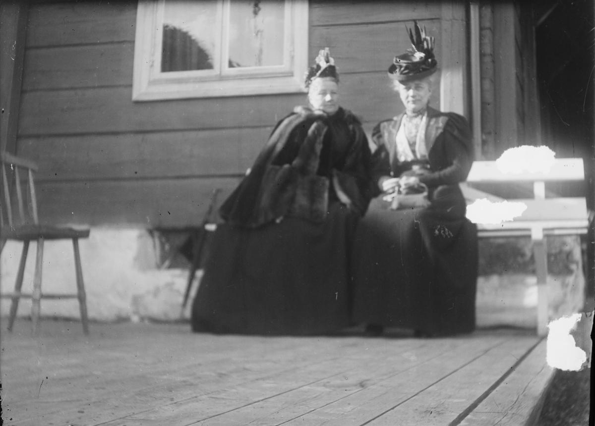 To damer, godt kledt, sitter sammen på en benk utenfor et hus. En vanlig kjøkkenstol står ved siden av dem på terrassen.