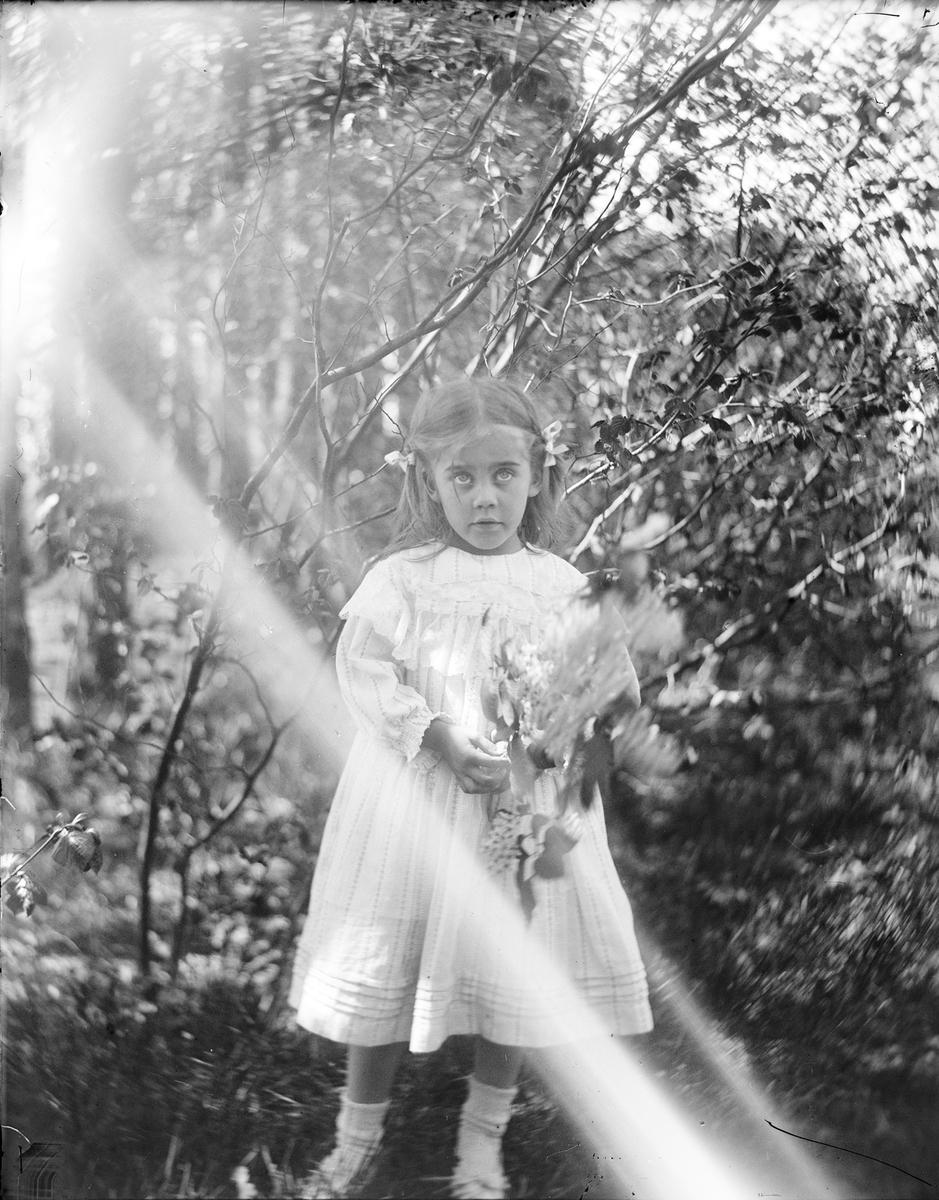 Louise (Ise) Mathiesen står på gresset med en bakgrunn av busker og trær. I hendene holder hun grener med blomster. Det er sommer.