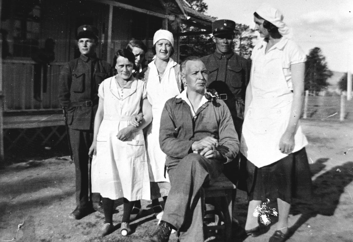 Et gruppebilde av kjøkkenbetjening og bestyrer av soldathjemmet i Nyborgmoen fotografert sommeren 1927. Fra venstre: Margit Joki, hennes søster Magnhild Joki og en ukjent dame til høyre. Foran dem sitter bestyrer Olav Korsvik som også var reisesekretær i  Norges Kristelig Ungdomsforbund. Bak damene som alle er kledd i hvite arbeidsklær står to unge soldater, personene ikke identifisert.