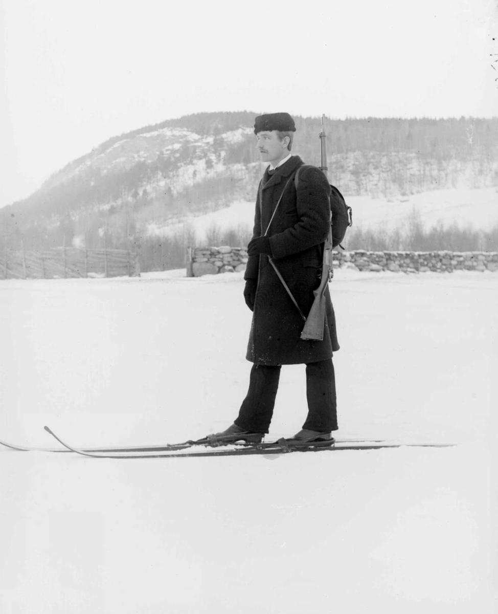Mann på ski med Krag-Jørgensengevær, jorde, steinmur