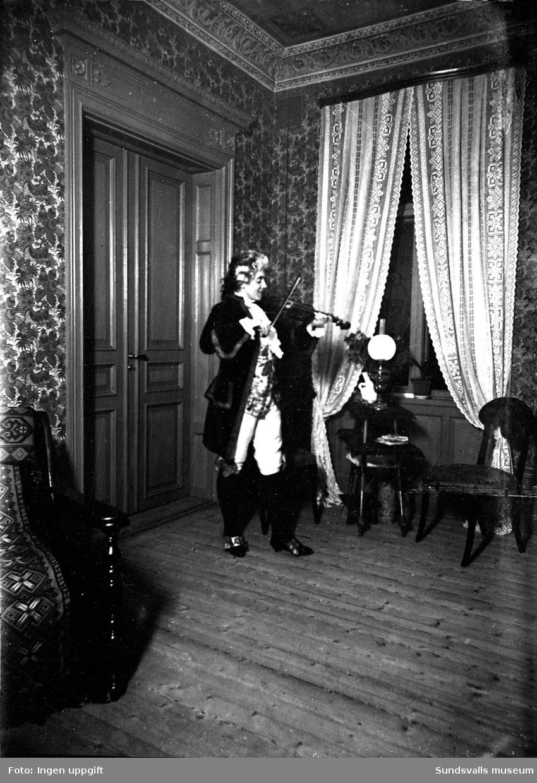 Utklädd person spelar fiol. Teaterföreställning?