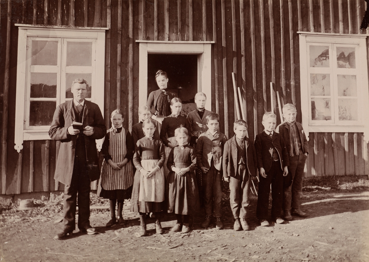 Gruppebilde fra Thorsø. En mann som holder en liten bok, syv jenter og fire gutter er stilt opp foran en dør.