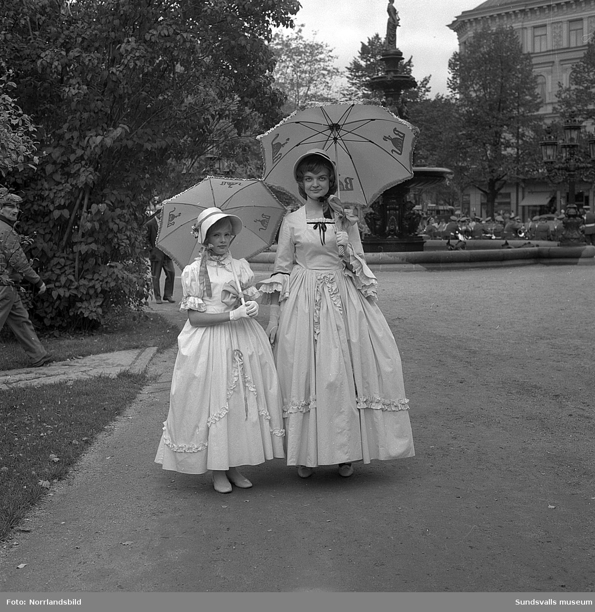 En ung kvinna och en flicka, båda klädda i gammeldags krinolin, gör reklam för Béves klädaffär.