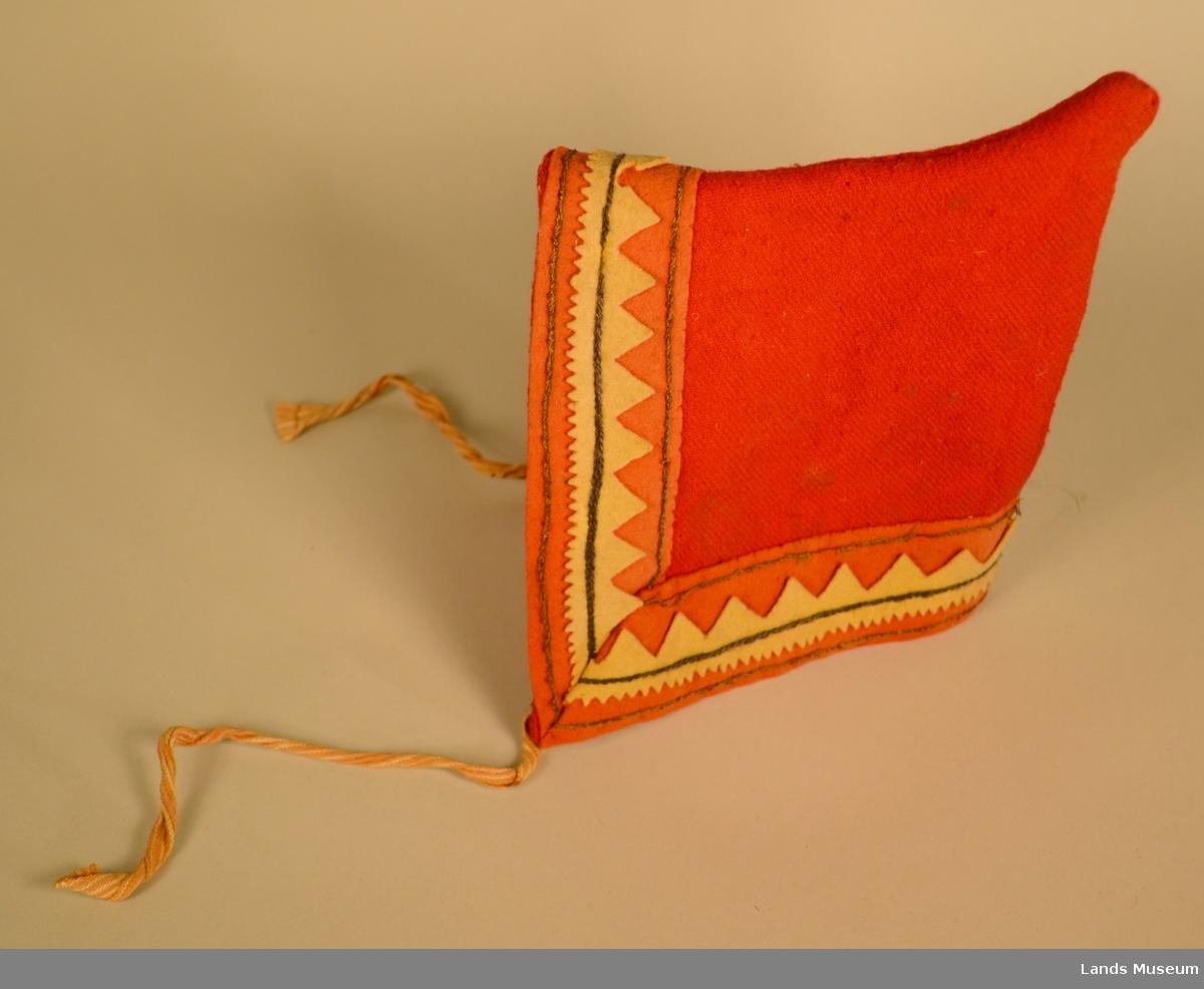 Kysen knytes under haka med to stripete band. Forma er trekantan med ei spiss opp bak. Dekor rundt kant; filt klipt i saksak og sydd på med ulltråd.