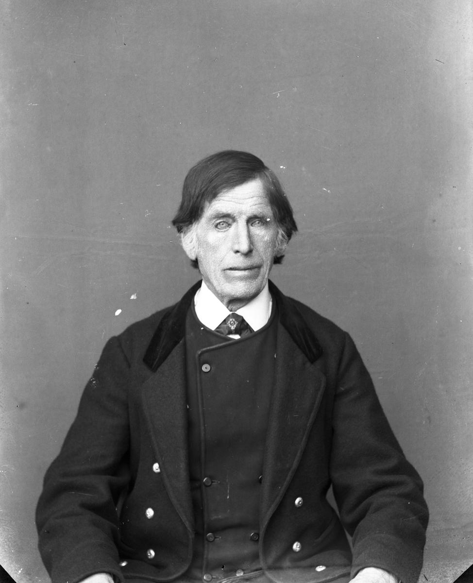 Mann kledd i kort jakke, sittende foran lerret, i halvfigur