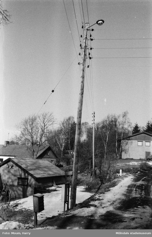 """Yngeredsfors Kraft AB utför elarbeten vid Södra Kyrkvägen i Kållered, år 1984. """"Det är ingen vacker syn med rader av elstolpar och trådar åt alla håll.""""  För mer information om bilden se under tilläggsinformation."""