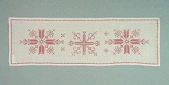 Avlång duk broderad med korsstygn. Broderad på halvblekt linne med tvåtrådigt bomullsgarn. Mönstret är i form av stjärnor.