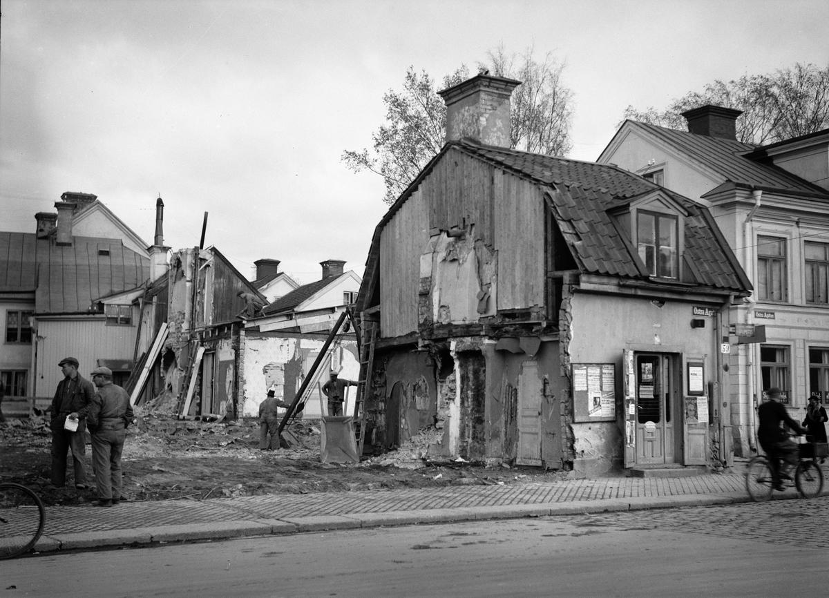 """Krogen """"Sju helvetes gluggar"""" rivs för att lämna plats för bygget av bostadsrättsföreningen Islandsgården, kvarteret Örnen, Östra Ågatan, Uppsala december 1935"""