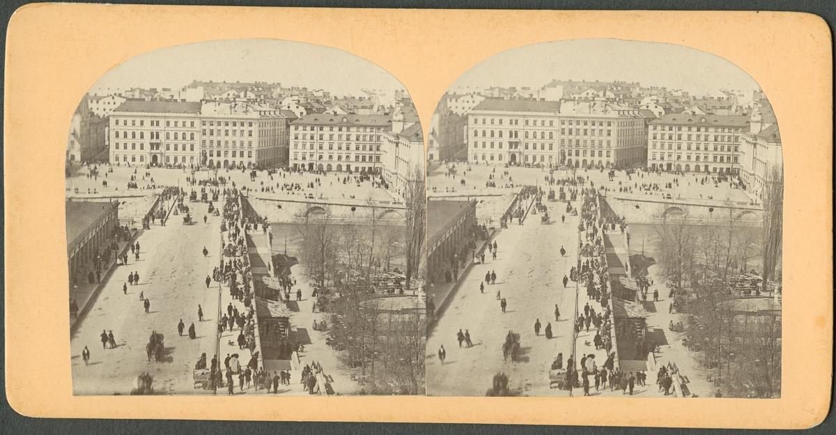 Stereobild med Stockholmsvy. Vy över Norrbro mot Gustav Adolfs torg. Möjligen vid tiden för Industriutställningen 1866.