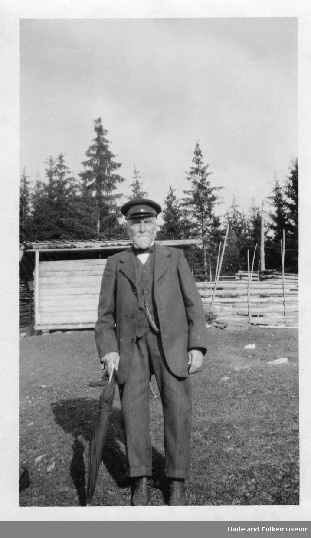Foto av mann i helfigur, støtter seg til en stokk (paraply). Mannen er Lars O. Smedsrud f. 1850