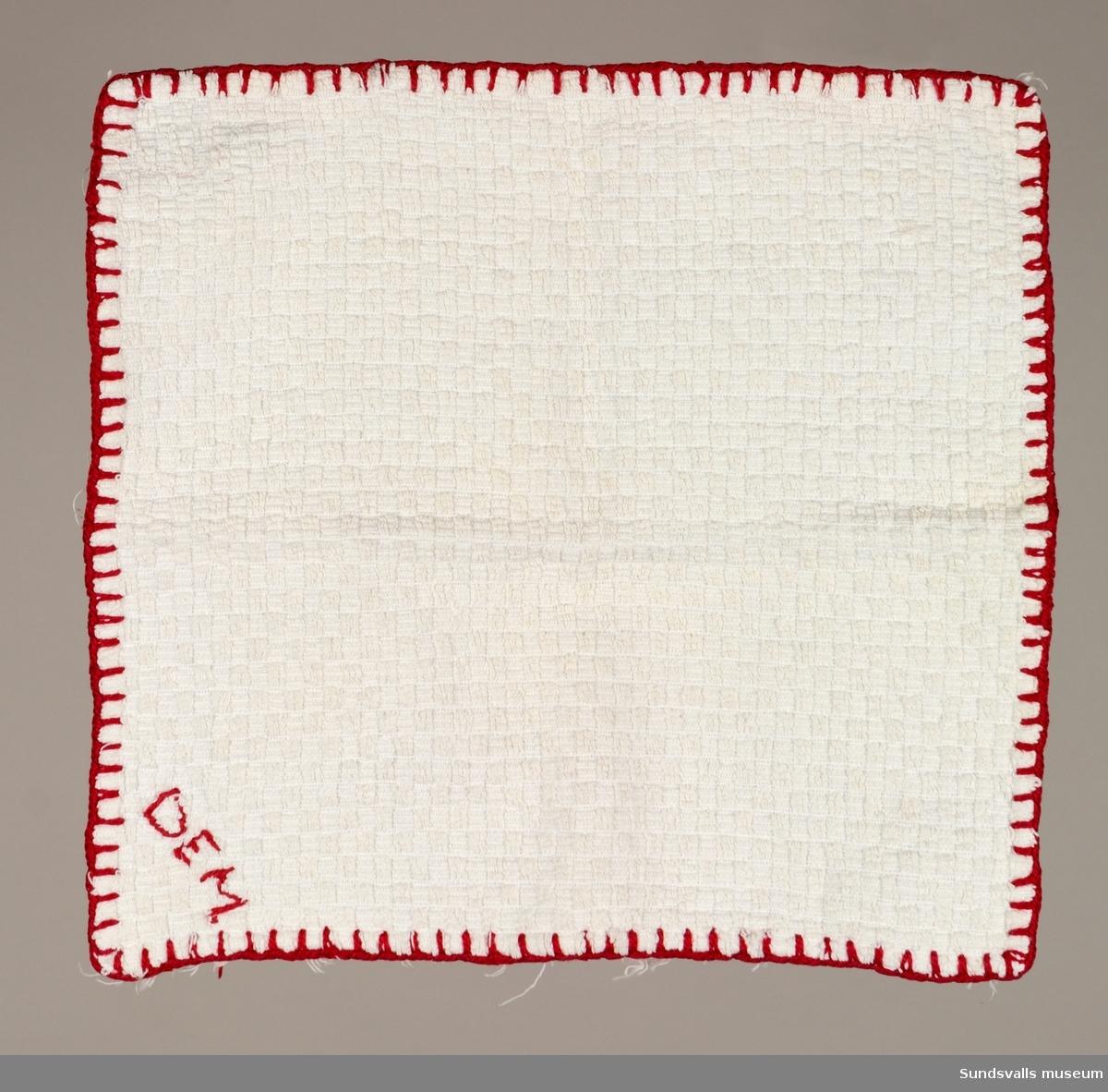 En kvadratisk tvättlapp med virkad kant och broderat monogram.