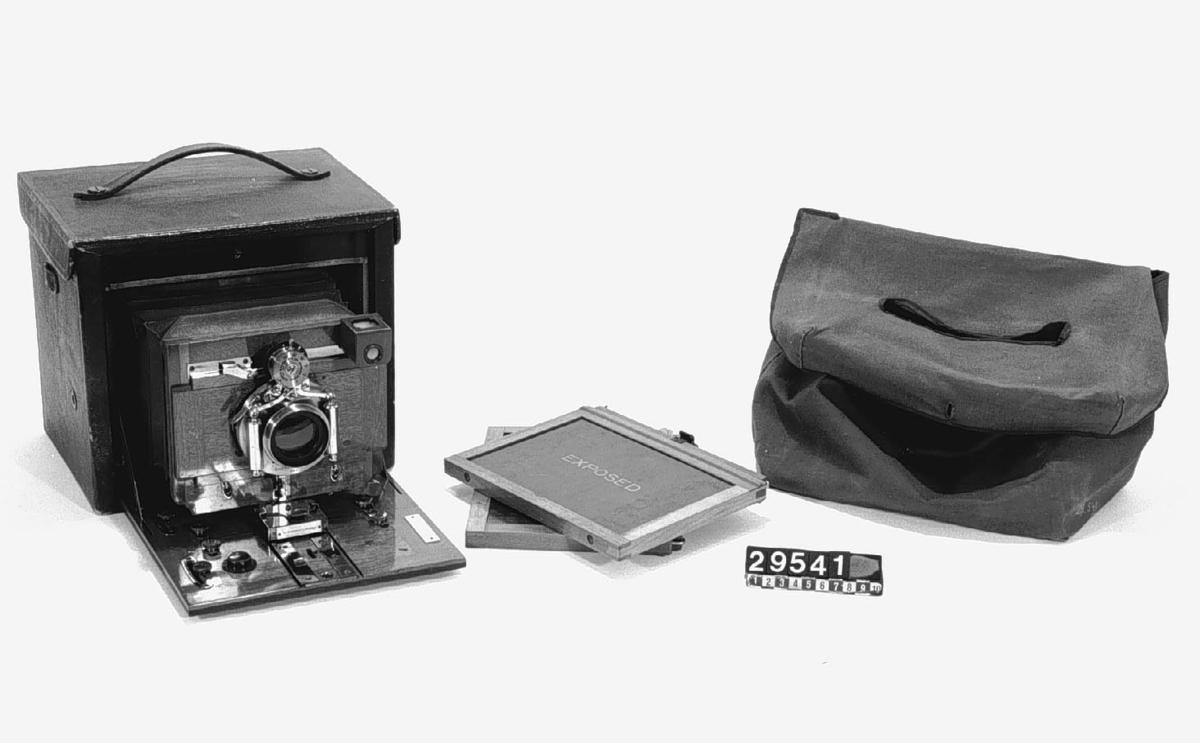 Klappkamera. Folding nr. 5 för plåtar 13 x 18 cm. Objektiv: Eastman Kodak Co. Pegamoidklätt kamerahus. Tillbehör: Tygfodral och 2 st. lösa träkasetter.