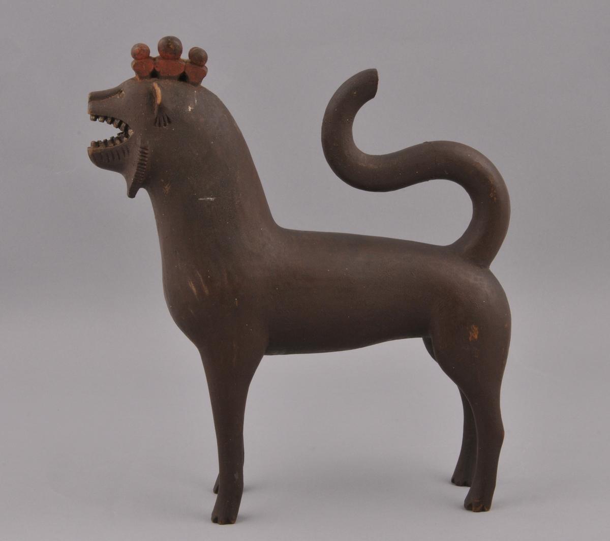 Løvefigur. Kroneliknande form på toppen, halen ligg fram over ryggen, skade og ein del borte. Figuren er måla brun, krona raud. Kan minne om ei akvamanile i form.
