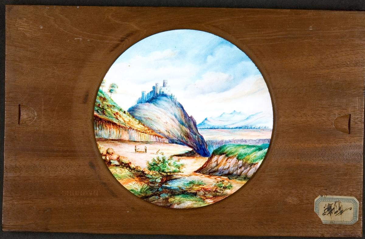 """Laterna magica bild målad i färg på glasskiva. """"Trachÿtspelare vid Wolkensburg på Silben=gebirge""""."""