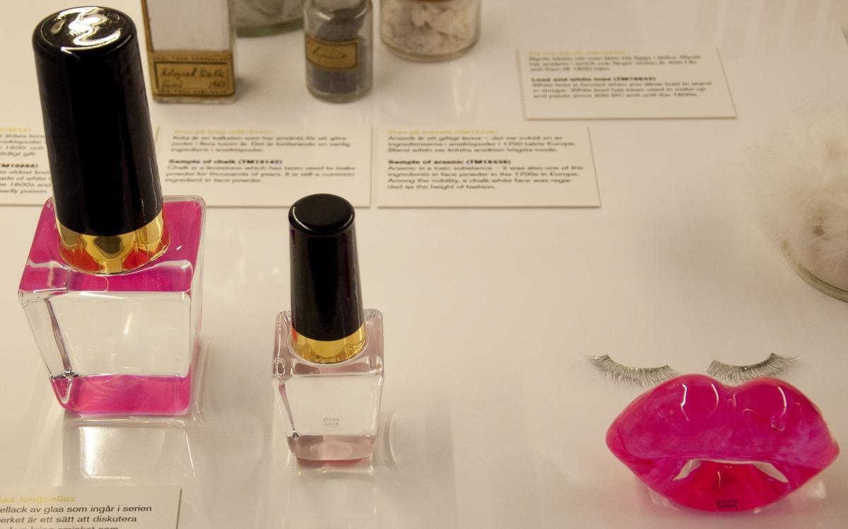 """Konstglas utformad som läppar, nagellack och läppstift. Ingår i Kosta Bodas serie """"Make up""""  i """"Limited Edition""""-sortimentet och är formgiven av Åsa Jungnelius.  Omfattar följande artiklar: - Hotlips, röda läppar, höjd 65 mm art nr 7091150 - Nailpolish, nagellackflaska """"neon pink"""" höjd 190 mm art nr 7091146 - Lipstick, läppstift """"neon pink"""" höjd 210 mm art nr 7091148 - Lipstick, läppstift """"pearl pink"""" höjd 210 mm art nr 7091149 - Lipstick, läppstift """"pearl pink"""" höjd 133 mm art nr 7091159 (2 st) - Lipstick, läppstift """"neon pink"""" höjd 133 mm art nr 7091158 - Nailpolish, nagellackflaska """"pearl pink"""" höjd 124 mm art nr 7091155 inklusive originalförpackningar."""