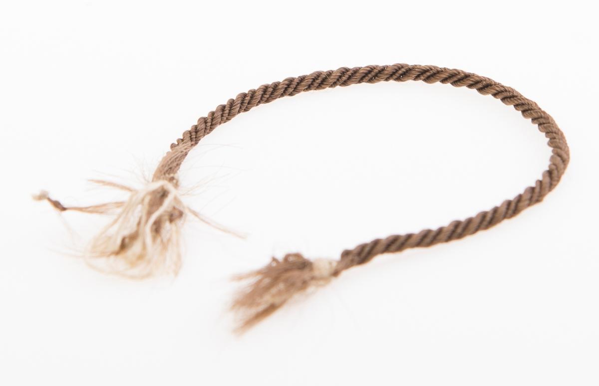 En lenke laget av brunt kvinnehår med tynn bommullstråd i hver ende. Lenken kan ha vært et armbånd. Teknikken er knipling, og lenken fremstår som en tett tvunnet snor.