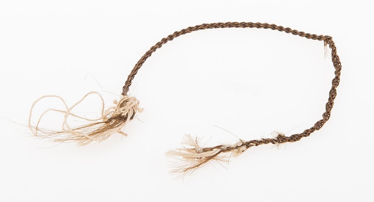 En tynn lenke laget av brunt kvinnehår med tynn bommullstråd i hver ende. Lenken kan ha vært et tynt armbånd. Lenken er gjort i to forskjellige teknikker.