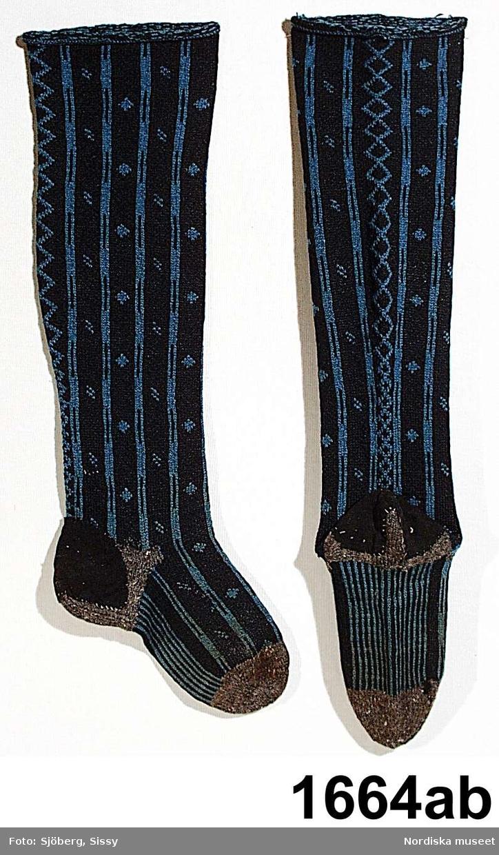 Ett par mansstrumpor slätstickade med mönsterbårder på längden i blått mot blåsvart botten, benet format med intagningar och utläggningar, foten smalrandig på undersidan, häl och tåparti stickat av ett ofärgat naturgrått ullgarn, troligen tillstickade efter slitage, slitlappar av svart ylletyg fastsydda på båda hälarna. Har enligt uppgift tillhört häradsdomaren Sven Johanssons i Sörkämsta bröllopsdräkt 1826. /Berit Eldvik mars 2005