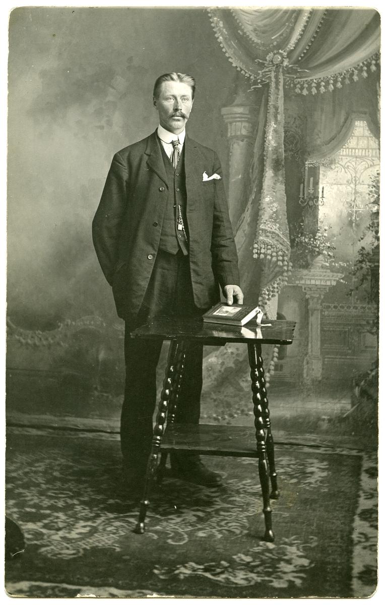 Portrett av mann i helfigur stående ved et bord. Han er kledd i dress og har slips og lommeur. Bildet er tatt i et atelier der lerretet viser et interiør. Kan det være fra Amerika?
