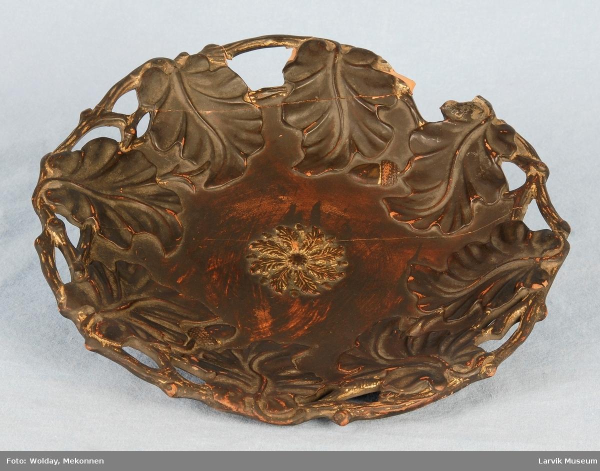 Form: gj.brutt kant med eikegrener og blader som peker mot midten. i bunnen rosett av eikeblader og nøtter forgylt. limt og naglet