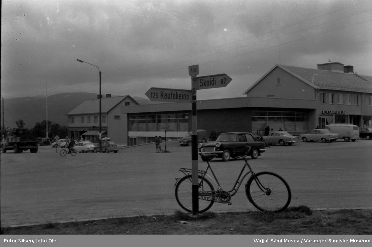 Bossekop i Alta. Alta Samvirkelag til høyre i bildet. Veiskilt med stedsnavn og avstand til Kautokeino og Skaidi i forgrunnen. Høsten 1966.
