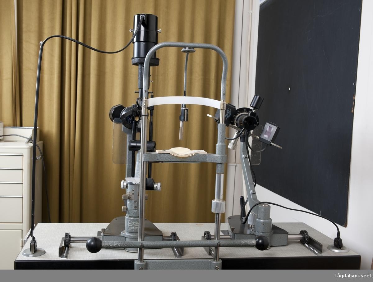 """Rektangulært respatexbord med målene 95x35 cm, og 77 cm høyt (slik det står nå) med hydraulisk hev- og senkfunskjon som betjenes med en fotpedal. Bordplaten står på en sokkel, med en sirkulær plate nederst med diameter 45 cm. Sokkelen er merket med """"JENA"""", og en etikett med teksten """"M. Gallus"""" er festet på fremsiden av bordplaten. Bordplaten er skyvbar mot høyre, da den står på et skinnesystem. En skuff under bordet på høyre side.   Innhold i skuff: 1 eske med fluorescein papir 2 objektiver 1 sett objektiv (16x). 2 speil 2 esker med lyspærer fra Haag-Streit AG 1 eske med lyspære fra Osram 2 metallstenger, den ene med kuleavslutning 2 pakker papirservietter fra Haag-Streit   På venstre side under bordplaten er en boks med hengslet lokk som kommer frem når man skyver bordplaten til høyre. Innhold: 1 instrumentdel med teksten """"Pat.no. 3070997 U.S.A. and other countries"""" og """"T90025948"""" (serienummer?) 1 plastboks med  plastflaske merket med Novasin, 1 glassflaske med ubestemmelig innhold (desinfeksjon). 1 liten plasteske med lokk med tilleggsutstyr til instrumentene. 1 sylinderformet plastboks med lokk merket med """"Ever clean"""". 1 pipetteflaske i glass. 1 sprayflaske for desinfeksjonsmiddel. 1 bruksanvisning for Pantasept (Haag-Streit).  På høyre side av boksen er en vribryter (merket med 5, 6 og 7,5 v) og en rød lampe. Strømledning for bordet på undersiden av bordplaten.   To instrumenter er montert på bordplaten, mens et stativ for pasientens hode er plassert på baksiden (pasientsiden) av bordplaten, slik at denne ikke er skyvbar men fast.   Mer informasjon kommer."""
