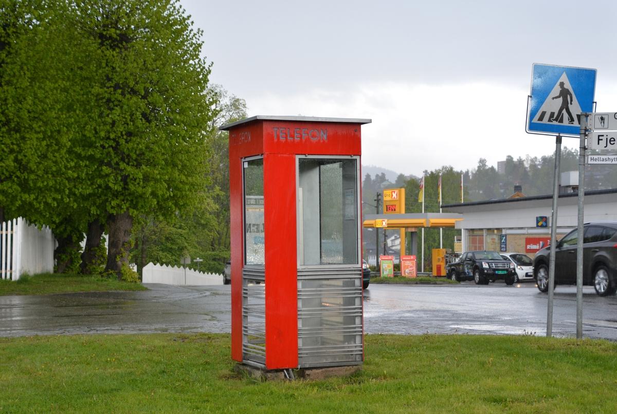 Denne telefonkiosken står ved Austad herredshus, Styrmoes vei 33, Drammen. Den er en av de 100 vernede telefokioskene rundt om i Norge. De røde telefonkioskene ble laget av hovedverkstedet til Telenor (Telegrafverket, Televerket) Målene er så å si uforandret.  Vi har dessverre ikke hatt kapasitet til å gjøre grundige mål av hver enkelt kiosk som er vernet.  Blant annet er vekten og høyden på døra endret fra tegningene til hovedverkstedet fra 1933. Målene fra 1933 var: Høyde 2500 mm + sokkel på ca 70 mm Grunnflate 1000x1000 mm. Vekt 850 kg. Mange av oss har minner knyttet til den lille røde bygningen. Historien om telefonkiosken er på mange måter historien om oss.  Derfor ble 100 av de røde telefonkioskene rundt om i landet vernet i 1997. Dette er en av dem.