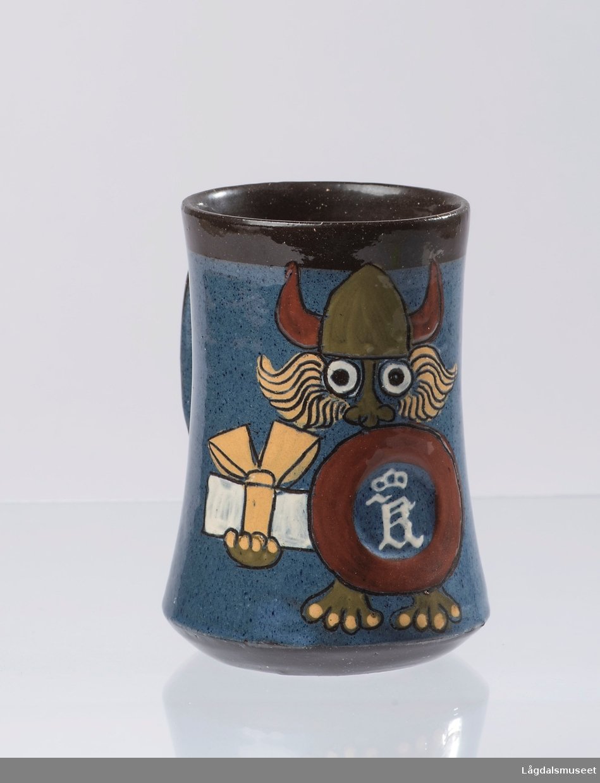 Ølkruset viser et motiv av en viking med logoen til Kongsberg Våpenfabrikk avbildet på skjoldet. Vikingen holder en innpakket presang i andre hånden.
