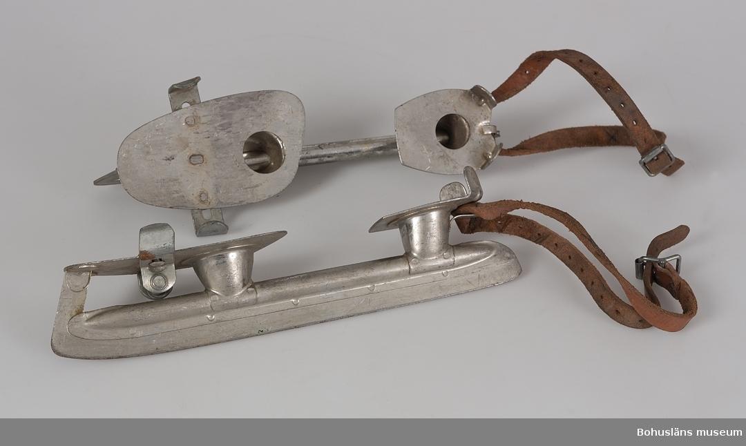 """Ett par skridskor bestående av enbart stålskenor med fotplattor och  läderremmar, s k """"halvrör"""". Skenan har två plattor, hålfoten saknar stöd. Den främre plattan har reglerbar bredd genom en skruvanordning undertill som reglerar de  två bleck som är avsedda att hålla fast kanten på den kraftiga pjäxan. Baktill hålls halvröret på plats genom en läderrem, ca 50 cm lång, som lindas runt benet och fästs med spänne. Halvrören motsvarar ungefär storlek 38,40. Under de främre fotplattorna står ingraverat: """"ABC-FABR: KUNGÄLV SWEDEN"""" runt fabrikens sexhörnade logo. Ishokeyrör med påsydd känga kallas helrör.  Litteratur:""""ABC-boken nr 82. Huvudkatalog sommaren 1956. Göteborg 1956.  Nordström, Thure: """"...att jobba te Claessons. En bok om ABC-fabrikerna."""" Kungälv 1990."""