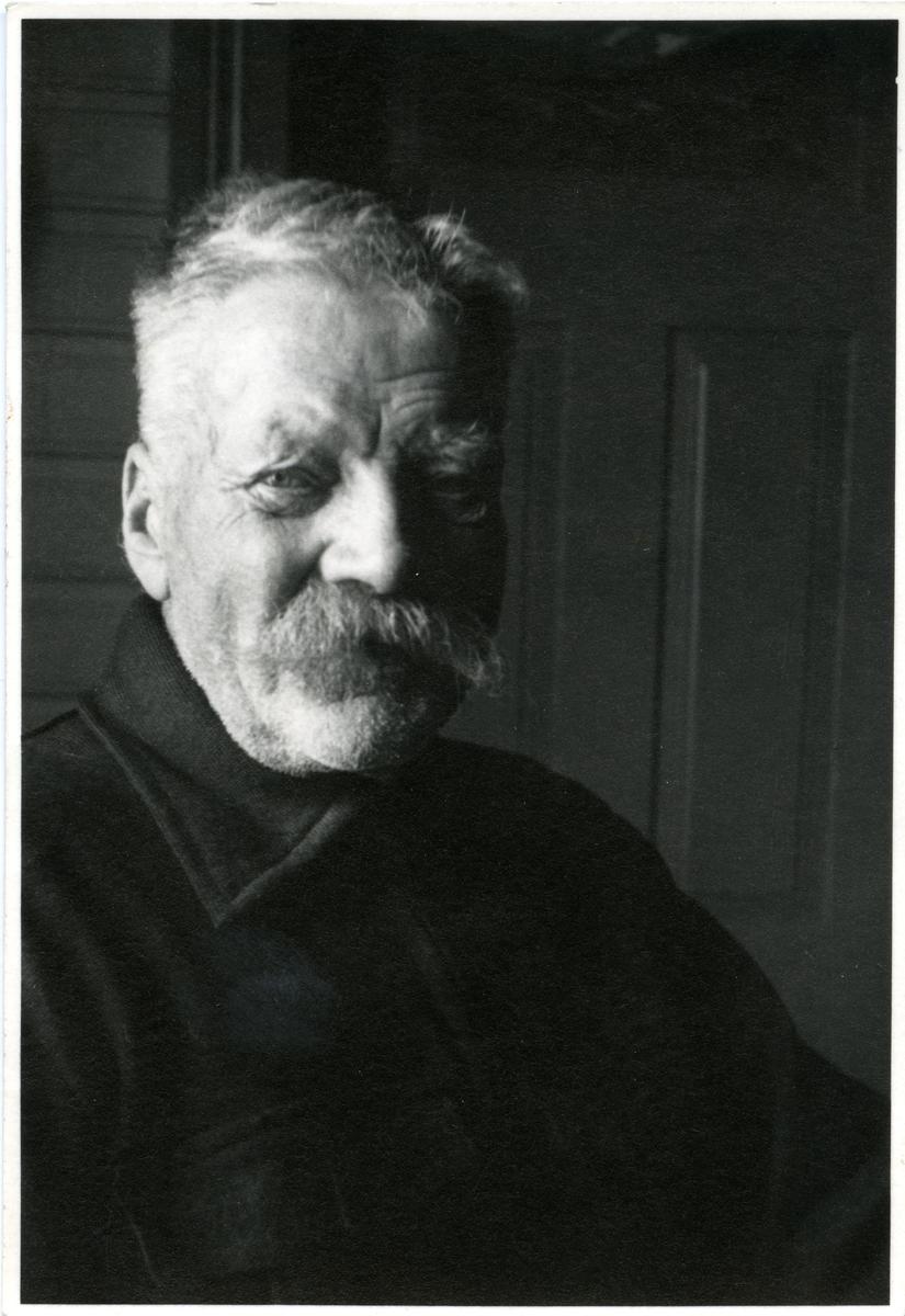 Portrett av en eldre mann sittende foran en vegg og dør. Mannen er iført en mørk, tykk jakke.
