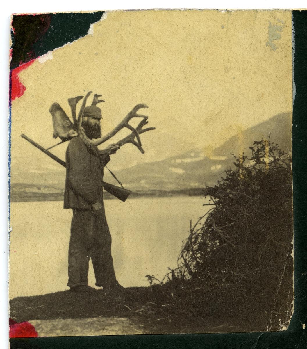 Portrett av en mann i helfigur med et reinsdyrhode over skuldrene. Mannen har også et gevær over den ene skulderen.