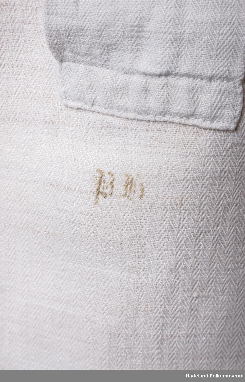 Mannsskjorte.  Hvitt kypertvevet bomullsstoff med bomullsrenning og lin islett. Håndvevd. Primærsnitt med halssplitt med stolpe med knapphull øverst. Linning med knapphull. Skulderstykke. Ermer med kile under rynket til ermlinning med knapphull. Splitt nederst i sidene. Stemplet I.H.
