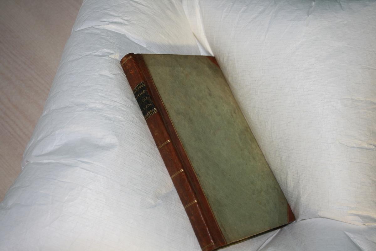 Lys grønt omslag av papp. Rygg og hjørner i brunt skinn. Kart til å brette ut foran tittelblad.