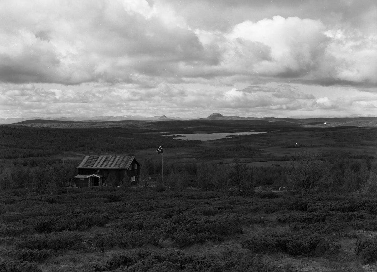 Gamle Lenningen fjellstue foran til venstre i bildet og fjelltoppene Rundemellen og Skarvemellen i bakgrunnen.