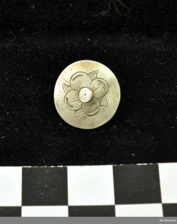 Rund, flat knapp med hempe i kobber, dekorert med firblada blomst med rund knapp i midten