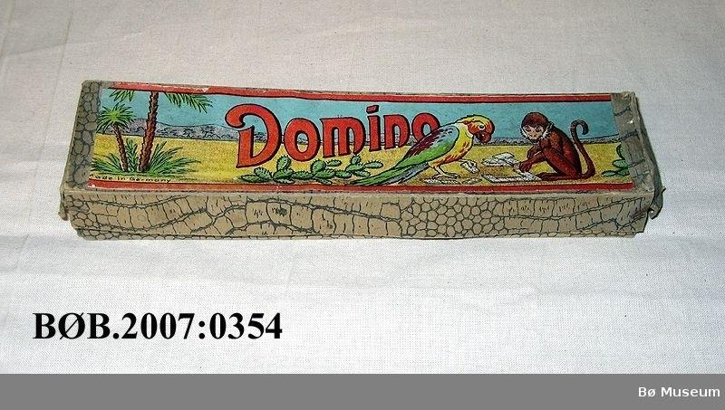 Motiv på loket: Papegøye og apekatt som spelar domino.