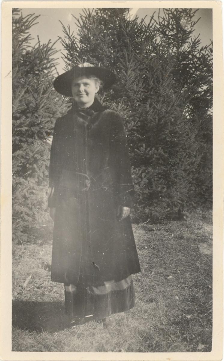 Ukjent kvinne i Amerika fotografert ute i naturen m. kåpe og hatt.
