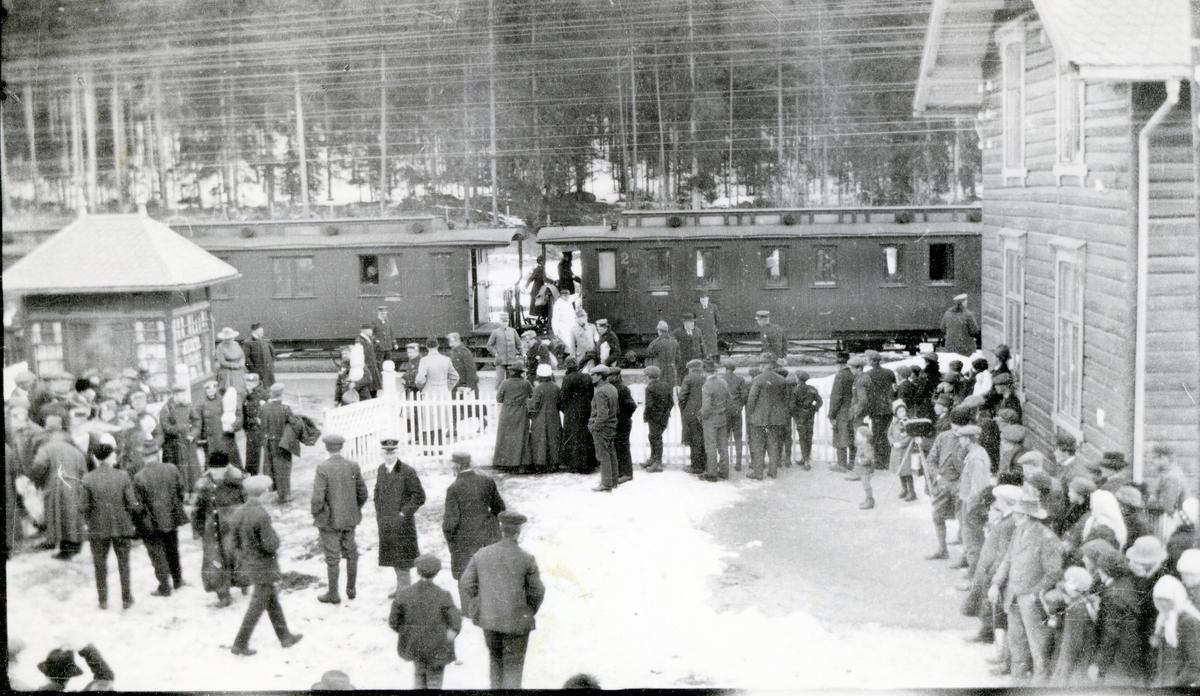Folkeliv på Fagernes stasjon, med stasjonsbygningen, Narvesen-kiosken og tog på perrongen
